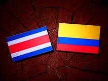 Costa Rican-vlag met Columbiaanse vlag op een geïsoleerde boomstomp stock illustratie