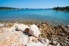 Costa rocciosa davanti al mare blu Fotografie Stock Libere da Diritti