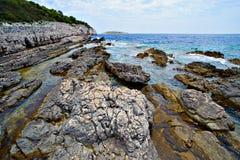 Costa rocciosa davanti al mare blu Fotografia Stock