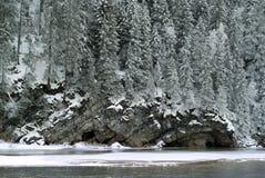 A costa rochosa do rio do inverno, coberto de vegetação com uma floresta coberto de neve Imagens de Stock