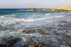 Costa rochosa, mar de turquesa com água espumosa, céu sem nuvens fotos de stock