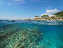 Costa rocosa con un faro y pescar mitad subacuática, partida de la visión por encima y por debajo de superficie del agua imágenes de archivo libres de regalías
