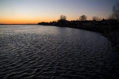 Costa rocosa de un río en la puesta del sol foto de archivo libre de regalías