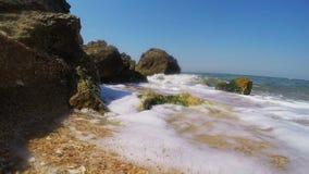 Costa rocosa e incidente espumoso de las ondas en el funcionamiento almacen de video