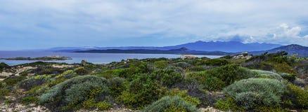 Costa rocosa, horizonte sobre el mar y las montañas abajo al agua Imagenes de archivo