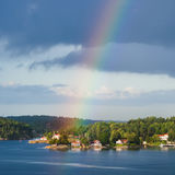 Costa verde con il villaggio ed arcobaleno in cielo blu Fotografia Stock Libera da Diritti
