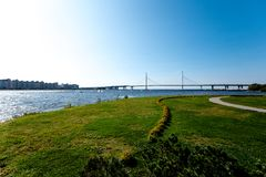 Costa verde del mar con el puente en mediodía imagen de archivo