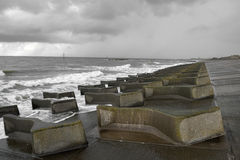 Costal Defences. Sea swell and stormy skies over man made abstract shaped concrete sea defences on the North Wirral coast line, near Liverpool, England UK Royalty Free Stock Photos