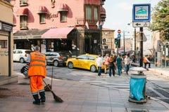 Costantinopoli, il 15 giugno 2017: portiere in uniforme luminosa dell'arancia che spazza le mattonelle sulla via nel distretto di Fotografia Stock Libera da Diritti