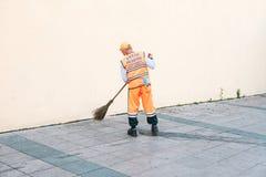 Costantinopoli, il 15 giugno 2017: portiere in uniforme luminosa dell'arancia che spazza le mattonelle sulla via nel distretto di Fotografie Stock