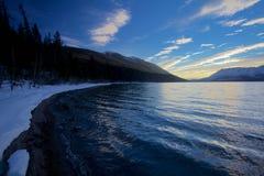 Costas nevado do por do sol da lavagem das ondas da calma do lago McDonald no parque nacional de geleira, Montana, EUA Imagem de Stock