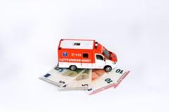 Coste de atención sanitaria: Coche de la ambulancia con el dinero euro Imágenes de archivo libres de regalías