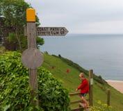 Costeggi il segno del percorso ed il giovane camminatore, Strete, Devon, Regno Unito Immagini Stock Libere da Diritti
