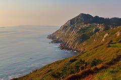 Costeie penhascos no crepúsculo em Costa da Vela, Galiza, Espanha imagem de stock