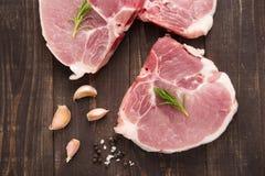 Costeleta de carne de porco crua da vista superior com alho e pimenta no backgrou de madeira imagens de stock royalty free
