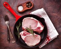 Costeleta de carne de porco crua em uma frigideira com alecrins, pimenta e sal fotos de stock royalty free