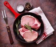 Costeleta de carne de porco crua em uma frigideira com alecrins, pimenta e sal imagem de stock