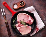 Costeleta de carne de porco crua em uma frigideira com alecrins, pimenta e sal fotografia de stock