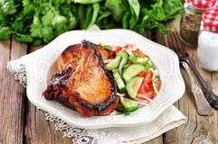 Costeleta de carne de porco grelhada com salada dos tomates, dos pepinos, das cebolas, da salsa e do azeite imagens de stock