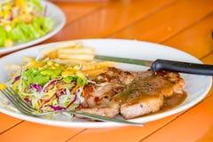 Costeleta de carne de porco grelhada suculenta (pescoço cortado) com salada Imagens de Stock