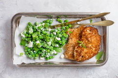 Costeleta de carneiro da galinha ou da carne de porco com queijo e salada das ervilhas foto de stock