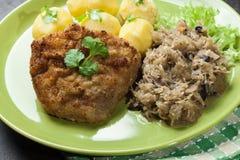 A costeleta de carneiro fritada da carne de porco serviu com batatas fervidas e fritou sauer Fotografia de Stock Royalty Free