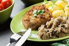 A costeleta de carneiro fritada da carne de porco serviu com batatas fervidas e fritou sauer Foto de Stock Royalty Free