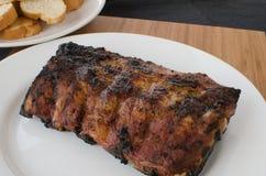 Costeleta de porco magra na grade com mergulho e o baguette brindado Foto de Stock