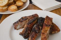 Costeleta de porco magra na grade com mergulho e o baguette brindado Imagens de Stock