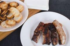 Costeleta de porco magra na grade com mergulho e o baguette brindado Imagem de Stock Royalty Free