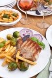 Costeletas de carne de porco com fritadas, couves de Bruxelas e vinho Foto de Stock