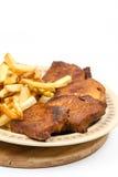 Costeletas de carne de porco cozidos com batatas fritas na placa imagens de stock