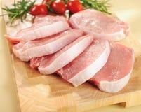 Costeletas de carne de porco cruas. Arranjo em uma placa de estaca. Imagens de Stock