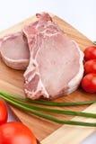 Costeletas de carne de porco cruas com os vegetais na placa de desbastamento Fotos de Stock Royalty Free