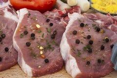Costeletas de carne de porco cruas e close up das especiarias Foto de Stock Royalty Free