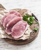 Costeletas de carne de porco cruas em uma placa de corte de madeira Fotografia de Stock Royalty Free