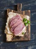 Costeletas de carne de porco cruas em uma placa de corte de madeira rústica Fotos de Stock Royalty Free