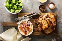 Costeletas de carne de porco grelhadas com salada do slaw do cole foto de stock royalty free
