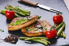 Costeletas de carne de porco grelhadas, bifes com vegetais, tomates, feijões e molho em uma ardósia preta Carne fresca com espuma Foto de Stock Royalty Free