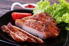 Costeletas de carne de porco grelhadas com tomate, alface de folhas e ketchup na placa fotografia de stock