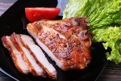 Costeletas de carne de porco grelhadas com tomate, alface de folhas e ketchup na placa fotografia de stock royalty free