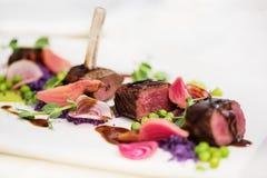 Costeletas de cordeiro com a ervilha batatas roxas imagem de stock royalty free