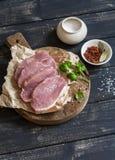 Costeletas e especiarias de carne de porco cruas em uma placa de corte de madeira rústica Fotos de Stock