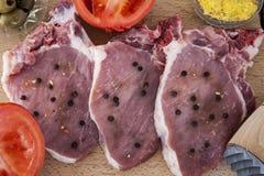 Costeletas e especiarias de carne de porco em uma placa de madeira Imagens de Stock
