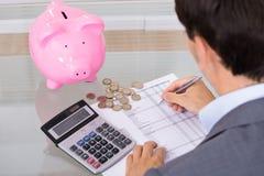 Costes del ahorro del hombre de negocios Foto de archivo