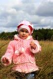 Costes del niño en una hierba seca Fotografía de archivo