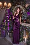 Costes morenos hermosos jovenes en un vestido largo violeta cerca de un abeto de la Navidad Cerca las velas y los regalos del bur Foto de archivo libre de regalías