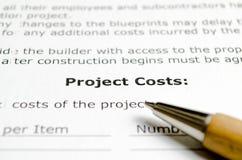 Costi del progetto con la penna di legno immagini stock