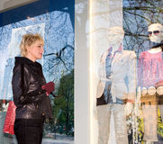 Costi della giovane donna nei negozi della via Immagine Stock