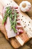 Costillas crudas del cordero con romero, pimienta y ajo en el tablero de madera foto de archivo